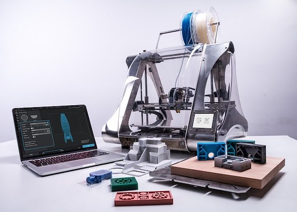 A 3D printer, 3D printed objects and a laptop.