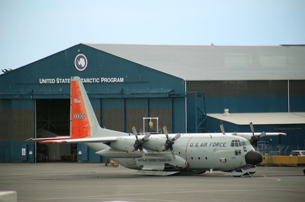 A U.S. Air Force aircraft, parked beside a building of the United States Antarctic Program.