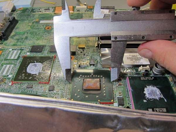 An engineer's first-person view as they use a caliper to measure an integrated circuit (mounted on a laptop's circuit board).