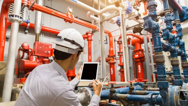 An engineer prepares his tablet to digitally inspect an industrial pump system.