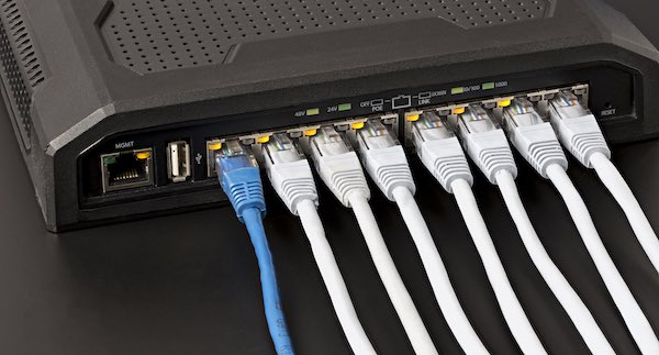 A close up of Ethernet cables connected to a PoE network switch.