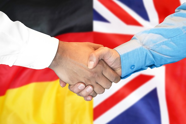 From one country to another: a handshake takes place, as the German flag and the UK flag combine in the background.