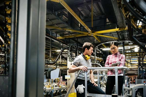 Two industry professionals discuss engineering notes in a manufacturing facility.