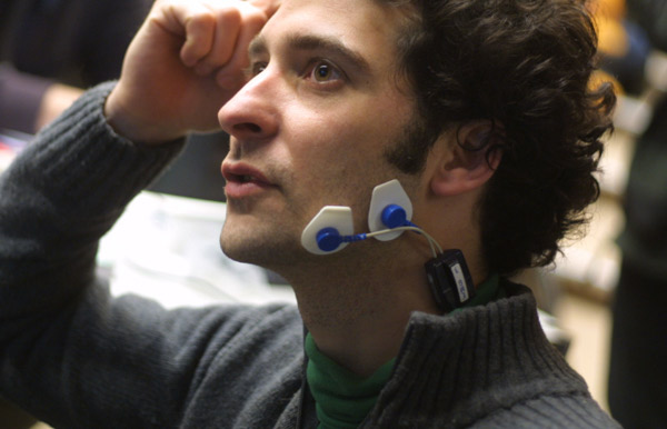A man trialling a wearable magnetic stimulation device, whose sensors are attached to his lower jaw