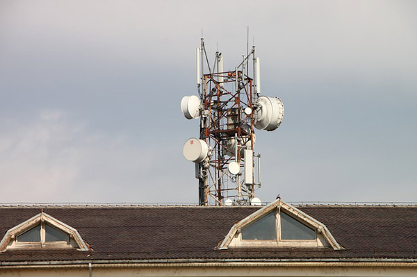 A typical, modern example of microwave technology: a microwave tower with four antennas, peeking over the roof of a building. Microwave towers are designed to be sufficiently high to provide a clear 'line of sight' for data transmission.