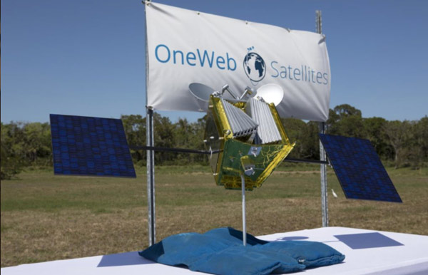 A banner that shows OneWeb Satellites logo. In front of it stands one of the company's constellation satellites.