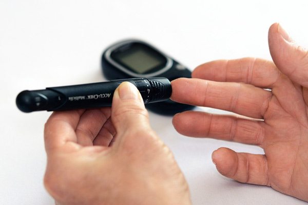 A patient's first-person view as he applies a portable blood glucose meter to his middle fingertip.