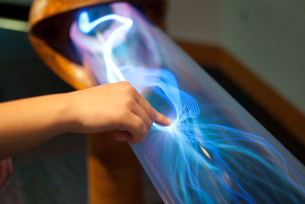 Will cutting-edge triboelectric technology soon be at our fingertips? Pictured: a user's touch adds to the static charge of electricity flowing through a tube.