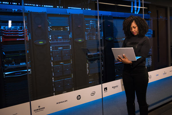 Learning on the job: a woman stands in a data centre while researching on her laptop.