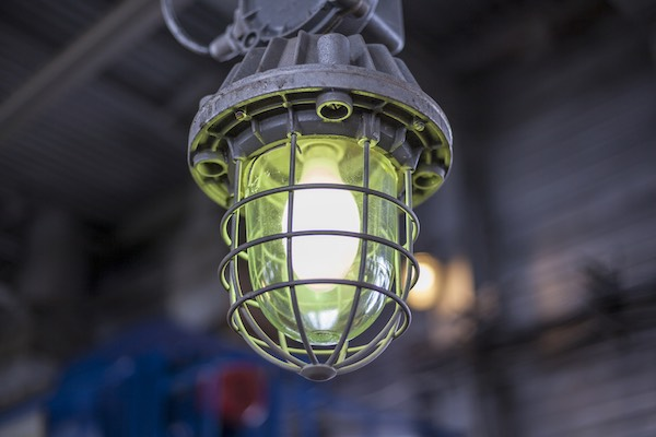 Compare and contrast intrinsic safety with explosion-proofing. Pictured: a close-up of an explosion-proof lamp in an industrial facility