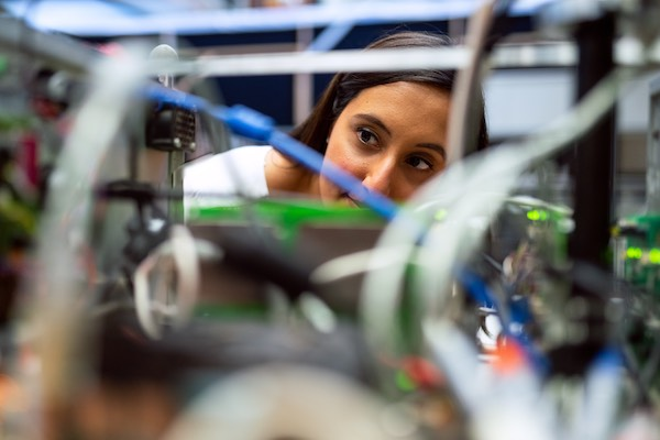 A female engineer working closely with equipment.