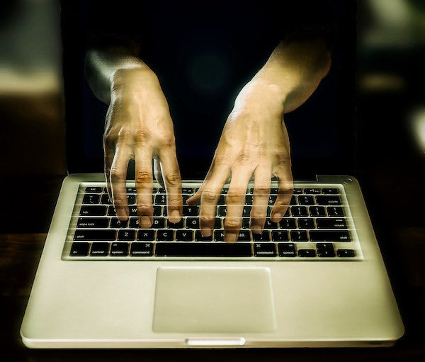 Ghostly hands appear from the wrong side of a laptop keyboard.